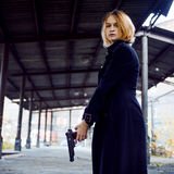 Woman pointing a gun. Mafia girl shooting at someone on the street. royalty free stock photography