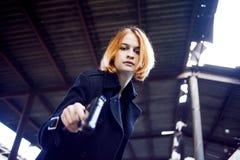 Woman pointing a gun. Mafia girl shooting at someone on the street. Stock Photos