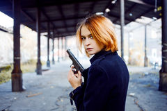 Woman pointing a gun. Mafia girl shooting at someone on the street. Royalty Free Stock Image