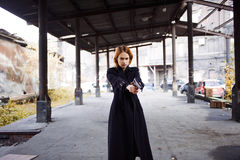 Woman pointing a gun. Mafia girl shooting at someone on the street. Stock Images