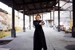 Woman pointing a gun. Mafia girl shooting at someone on the street. Royalty Free Stock Photos