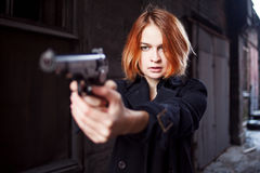 Woman pointing a gun. Mafia girl shooting at someone on the street. Emotion of fear, fright Royalty Free Stock Photo