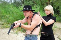 Woman pointing gun at shirtless man royalty free stock images