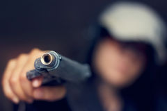 Woman pointing a gun at the target on dark background Stock Images