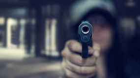 Woman pointing a gun at the target on dark background, soft focus Royalty Free Stock Photography