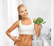 Woman pointing at her abs and holding broccoli Royalty Free Stock Images