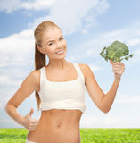 Woman pointing at her abs and holding broccoli Royalty Free Stock Image
