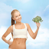 Woman pointing at her abs and holding broccoli Royalty Free Stock Photography