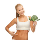 Woman pointing at her abs and holding broccoli Stock Photo