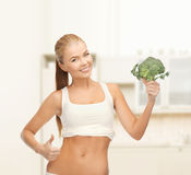 Woman pointing at her abs and holding broccoli Royalty Free Stock Photo