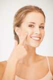 Woman pointing at her cheek Royalty Free Stock Photos