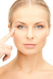 Woman pointing at her eye area Stock Images