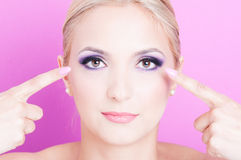 Woman pointing her eyes as professional make-up concept. On pink background Royalty Free Stock Photo