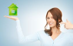 Woman pointing her finger at green eco house Stock Photos