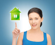 Woman pointing her finger on green house Royalty Free Stock Photos