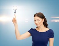 Woman pointing her finger at light bulb Royalty Free Stock Photo