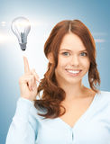 Woman pointing her finger at light bulb Royalty Free Stock Photography