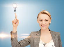 Woman pointing her finger at light bulb Stock Photo