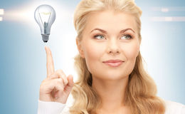 Woman pointing her finger at light bulb Royalty Free Stock Images