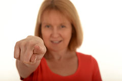 Woman pointing with her finger. Portrait of a smiling woman pointing with her finger, focus on the finger in the foreground Stock Image