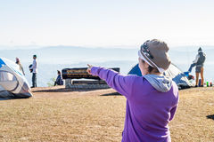 Woman is pointing her index finger to the mountain range Stock Photography