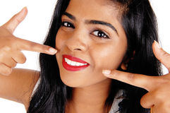 Woman pointing at her white teeth. stock photography