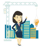 Woman pointing at idea bulb hanging on crane. Woman pointing at idea light bulb hanging on crane. Architect having excellent idea in town planning. Concept of Stock Images