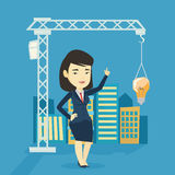 Woman pointing at idea bulb hanging on crane. Young asian woman pointing at idea light bulb hanging on crane. Architect having excellent idea in town planning Royalty Free Stock Image