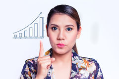 Woman pointing at increasing bar graph. Young pretty woman pointing at increasing bar graph Royalty Free Stock Photo