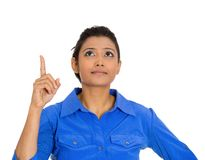Woman pointing with index finger and looking upwards. Closeup portrait of serious pretty beautiful woman pointing with index finger and looking upwards, isolated Stock Photography