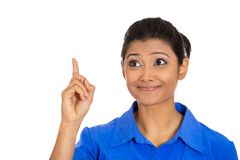 Woman pointing with index finger up and looking away or having the right answer. Closeup portrait of smiling pretty woman pointing with index finger up and Stock Images