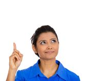 Woman pointing with index finger up and looking away or having the right answer. Closeup portrait of smiling pretty woman pointing with index finger up and Royalty Free Stock Image