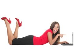 Woman pointing at laptop. Woman surprised lying down on the floor with her laptop. Pointing at the computer being shocked and happy excited. Beautiful cute young Royalty Free Stock Images