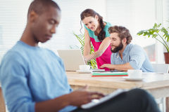 Woman pointing at laptop while discussing with man at desk Stock Image