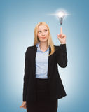 Woman pointing at light bulb. Business, energy and environment concept - woman pointing at light bulb Royalty Free Stock Photos