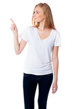 Woman pointing and looking at copyspace Royalty Free Stock Image