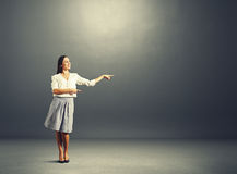 Woman pointing and looking at empty copyspace Royalty Free Stock Photos