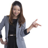 Woman pointing and looking to the side. Casual young businesswoman in white shirt looking, pointing and smiling at copy space. Young mixed race chinese / Royalty Free Stock Photos
