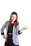 Woman pointing and looking to the side. Casual young businesswoman in white shirt looking, pointing and smiling at copy space. Young mixed race chinese / Royalty Free Stock Images