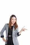 Woman pointing and looking to the side. Casual young businesswoman in white shirt looking, pointing and smiling at copy space. Young mixed race chinese / Royalty Free Stock Photography