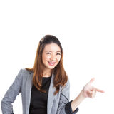 Woman pointing and looking to the side. Casual young businesswoman in white shirt looking, pointing and smiling at copy space. Young mixed race chinese / Stock Photos