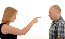 Woman pointing at a man. Side portrait of a woman pointing at a middle aged man with a white background Royalty Free Stock Photography