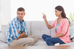 Woman pointing at man while sitting on sofa Stock Photos