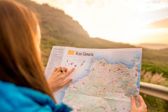 Woman pointing on the map of Gran Canaria island. Female hands pointing on the map of Gran Canaria island on the mountain background stock photo