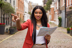 Woman pointing with map Royalty Free Stock Images