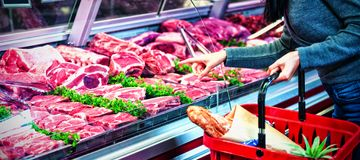Woman pointing at meat in display royalty free stock photography