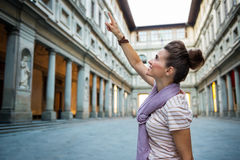 Woman pointing near uffizi gallery in florence. Young woman pointing near uffizi gallery in florence, italy royalty free stock photography