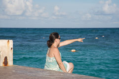 Woman pointing by the ocean Royalty Free Stock Images