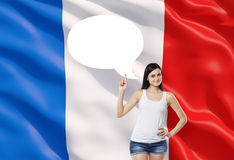 Woman is pointing out the empty thought bubble. French flag as a background. Beautiful woman is pointing out the empty thought bubble. French flag as a Stock Image