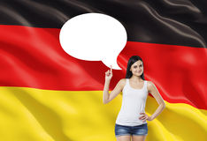Woman is pointing out the empty thought bubble. German flag as a background. Stock Photos
